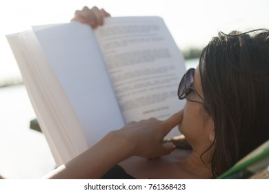 Young woman with sunglasses reading a book outdoors by the river, soft focus