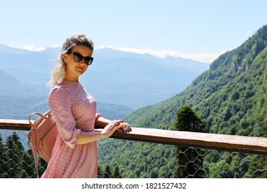 Young woman in sunglasses stands on the observation deck against the background of mountains on a summer sunny day