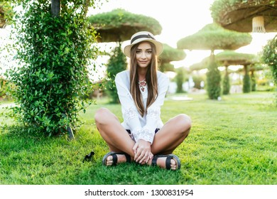 Young woman in sunglasses and straw hat sitiing on grass at resort hotel park