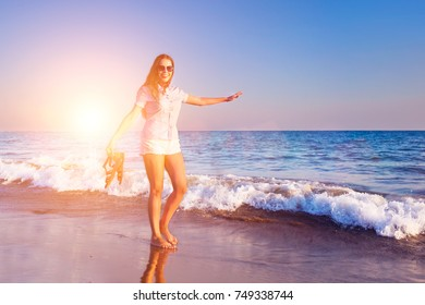 Young woman in sunglasses walking on a sea shore