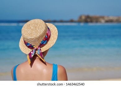 Young woman in sunhat relaxing on beach during summer vacation. She is against blue sea water on sunny day.