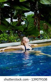 Young woman in sunny day in tropic resort with swimming pool