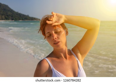 Young woman with sunstroke and headache. Woman on hot beach suffer of heat. Health problem on holiday. Medicine on vacation. Dangerous sun. Beach life. Sun stroke on sunny beach. Healthcare in tropics
