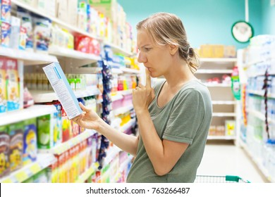 Young woman in supermarket groceries carefully reading nutrients of cornflakes quick breakfast. Healthy eating concept