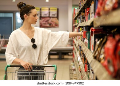 Young woman in supermarket with shopping cart