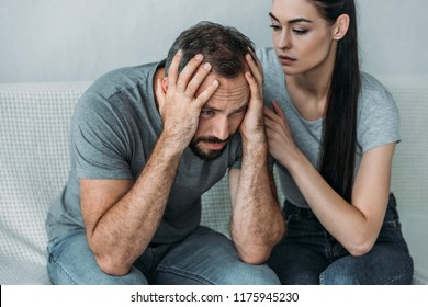 young woman supporting depressed frustrated boyfriend sitting on couch