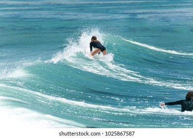 Young woman surfer flops down onto her board after missing a wave