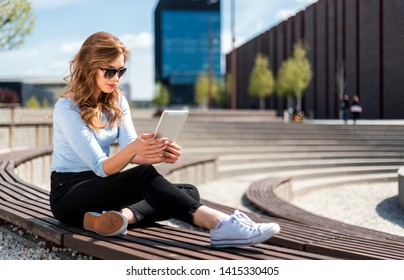 Young woman surfing the internet using tablet at free wifi area in city space
