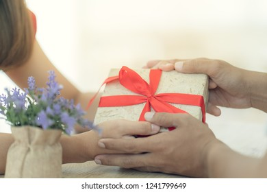 Young woman surprise her boyfrind by give a present gift on the wedding anniversary
