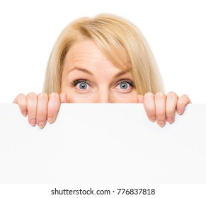 Young woman with surprised eyes peeking out from behind billboard paper poster. Businesswoman holding big white banner, isolated on white background.