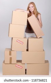Young woman surrounded by cardboard boxes