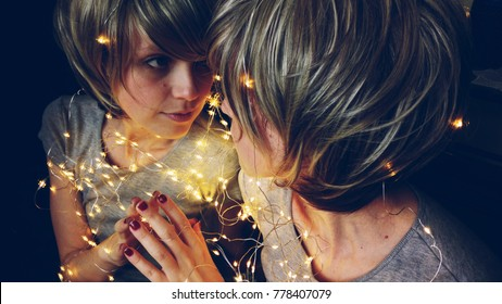 Young woman surrounded by christmas lights reflected in a mirror