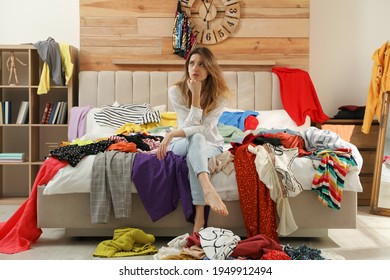 Young woman surrounded by different clothes in messy room. Fast fashion concept