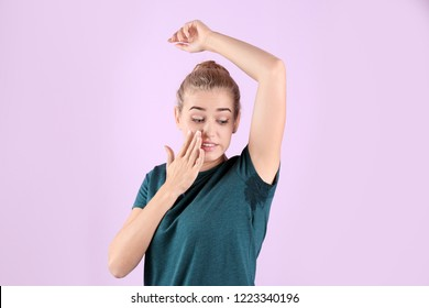 Young woman with sweat stain on her clothes against color background. Using deodorant
