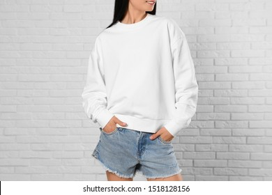 Young woman in sweater at brick wall, closeup. Mock up for design