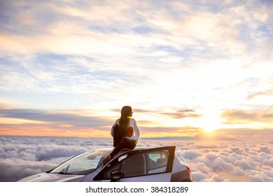 Young woman in sweater with heart shape enjoying beautiful cloudscape sitting on the car roof above the clouds on the sunrise. Wide angle image with a lot of space