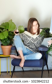 Young woman in sweater using tablet and drinking red wine chilling in armchair.
