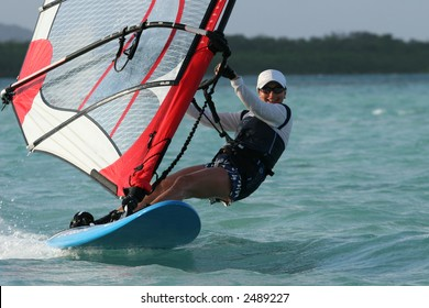 A young woman sweeping over a blue lagoon on a windsurfer