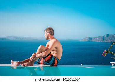 young woman in the swimming pool relaxing looking out over the ocean caldera of Oia Santorini Greece, man relaxing in infinity swimming pool looking at the sea