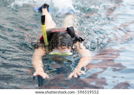 1c095fb03923 Young woman swimming underwater in the pool wearing snorkel and scuba shoes  (drive slippers