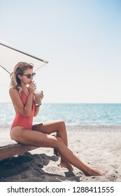 Young woman in swimsuit with cocktail glass on white beach sitting on sunbed