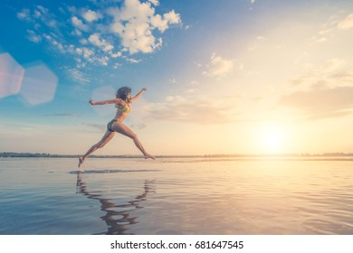 Young woman in a swimsuit with curly hair running on water against the backdrop of blue sky with clouds