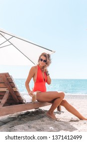 Young woman in swimsuit with milkshake on white beach sitting on sunbed
