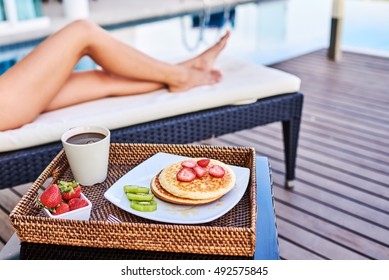 Young woman in swimsuit relaxing with morning coffee.