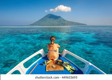 Young woman in swimsuit sit on boat with a mask and flippers looking to a clean sea and volcano Manado Tua. North Sulawesi, Indonesia.