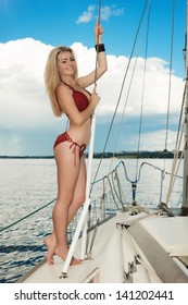 Young woman in swimsuit standing on yacht at sunny day