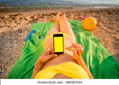 Young woman in swimsuit using mobile phone with empty screen for copy paste lying on the green towel on the beach. Top view focused on the hand with phone.