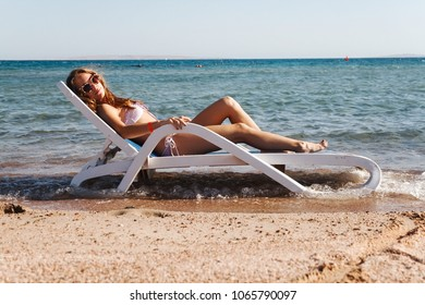 Young woman in a swimsuit wearing sunglasses lies on a deckchair in the sea. Concept life style.