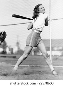 Young woman swinging a baseball bat in a baseball field