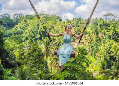 Young woman swinging in the jungle rainforest of Bali island, Indonesia. Swing in the tropics. Swings - trend of Bali