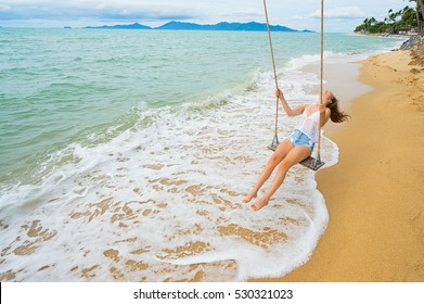 Young woman swinging on a beach swing. Selective focus. Hairs in motion blur.