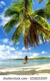 Young woman swinging on a rope swing (blurred motion) at the beach, Nananu-i-Ra island, Fiji. Tourism is the main industry of Nananu-I-Ra