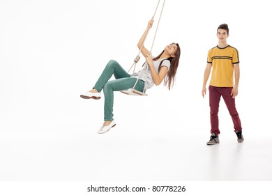 young woman swinging on a swing with handsome man looking