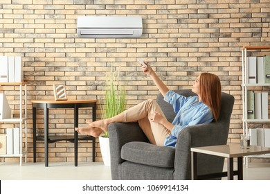 Young woman switching on air conditioner while sitting in armchair at home