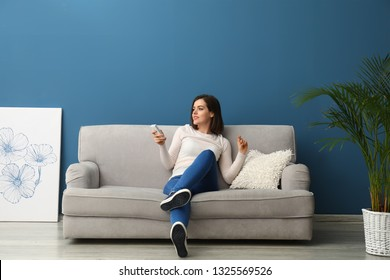 Young woman switching on air conditioner at home