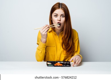 Young woman at a table eating sushi white space, white background, woman eating sushi.