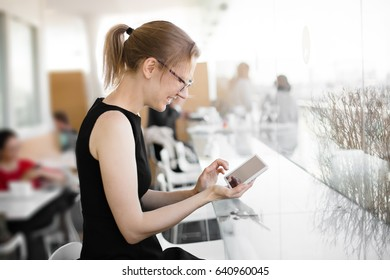 Young woman with a tablet in business office background