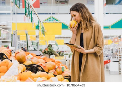 Young woman with a tablet smells grapefruit, picks food in a supermarket