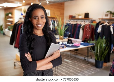 Young woman with tablet smiling to camera in a clothes shop