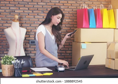 Young woman tailor with laptop is answering emails, Business woman entrepreneurial success . Sales Online Parcel delivery