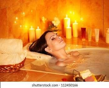 Young woman take bubble  bath with candle.