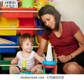 Young woman take care of baby. Playing with toys in daycare