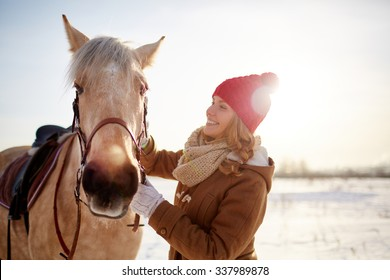 Young woman take care of her horse