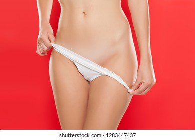 Young woman take off her nanties and showing her waxed pubic hair on red background