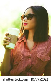 Young woman with take out coffee in the summer