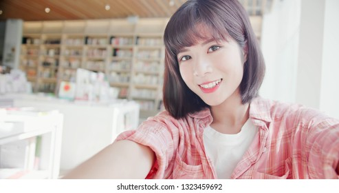 young woman take a selfie by smart phone indoor